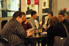 Six persons sitting around a round table drinking beer and talking