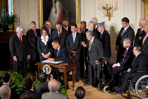 Speaker Nancy Pelosi watches as President Obama signs the bill into law