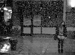 Stand in the Rain (Alyssa L. Miller) Tags: street shadow blackandwhite bw white chicago black window wet glass girl rain weather night contrast corner dark geotagged person photography evening droplets drops waiting downtown alone cityscape chaos gloomy darkness streetlights circles sony perspective streetphotography surreal dreary pedestrian stormy cybershot stranger drop safety hidden sidewalk shade raindrops despair lonely through dots obscured sonycybershot longing obscure drenched windowshot mostexcellent ocfd conceptphotos alyssafilmmaker alyssalmiller dwcffbw