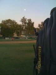 Catching balls in the outfield on a beautiful night at Alex's baseball practice