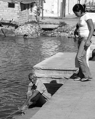 Girl watches man fishing (steverichard) Tags: man water port photography bay fishing fisherman child steve cuba cigar images richard caribbean pecheur cienfuegos kuba cubano steverichard wwwsrichardimagescom