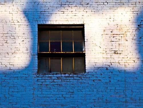 graffiti around a window: sky-blue painted brick, and a few white-painted clouds