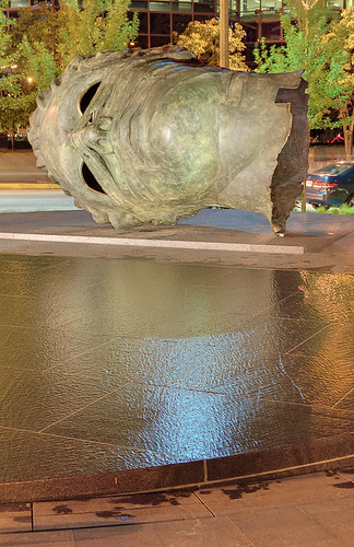 "Bronze sculpture, ""Eros Bendato"" (Eros Bound) by Igor Mitoraj, with scrim fountain in foreground, at the Citygarden, in Saint Louis, Missouri, USA - view at night"