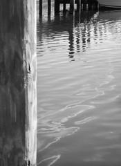 Oil Slick (scilit) Tags: blackandwhite monochrome reflections dock minimalism tqm oilslick northport boatramp linesandcurves theworldwelivein blackwhitephotos january2010 doublethebeauty freshwatercanal trolledproud 1001nightsmagiccity woodpilons