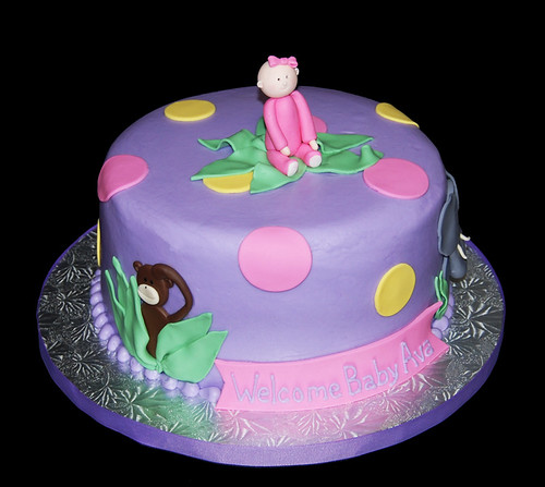 purple yellow and pink jungle themed baby shower cake with a monkey elephant and baby girl topper