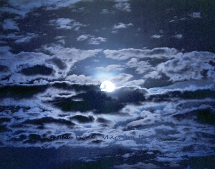 The full moon at twilight is reflected in a cloudy sky and is presented in a monochromatic blue.