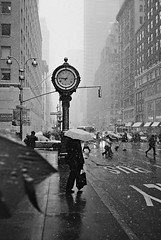 city winter (ho_hokus) Tags: street nyc newyorkcity winter snow newyork clock monochrome umbrella olympusstylusepic manhattan streetphotography 5thavenue olympus stylus newyorksnow ny2010