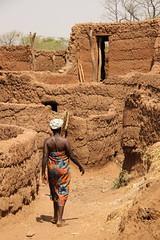 Woman walking along a traditional mud brick village (Raphael Bick) Tags: africa travel burkina fao