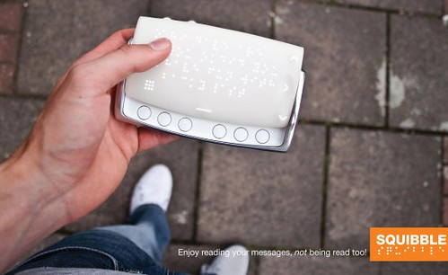 photo of large pocket-sized electronic device with a braille display and a series of buttons. Captioned Enjoy reading your messages, not being read to!