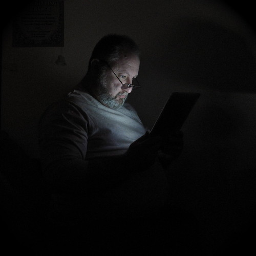 Man and iPad - man using Apple iPad to read while he sits in the dark