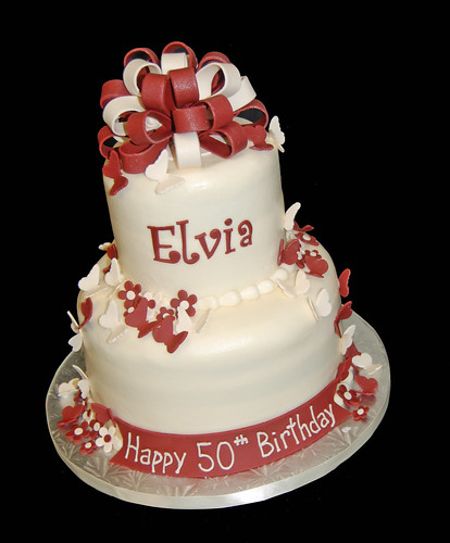 ivory and wine colored 2 tier 50th birthday cake with butterflies and multiloop bow