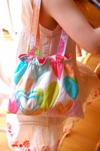 little girl holding fabric purse