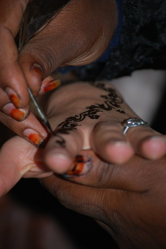 Woman drawing a henna tattoo on Isabelles hand