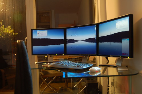 tri-monitors on glass desk