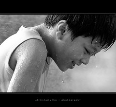when autumn rains fall (alvin lamucho ) Tags: park autumn light boy blackandwhite bw fall wet water smile rain contrast gladness happy child joy middleeast happiness drop glad jed droplet kuwait cheerful soaking drenched blackframe autumnrain canon450d rebelxsi alvinlamucho arylljed
