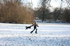 Menininha corre com cãozinho na neve no Vondelpark em Amsterdam