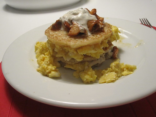 Rösti napoleon made with scrambled eggs and chanterelles, topped with dill sour cream