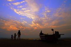 Watching the sunset (shankygup) Tags: ocean family sunset sea sun india beach water kids clouds children boat sand goa calangute beachsunset