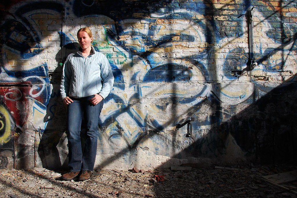 Sarah standing against a graffiti-covered wall, with light and shadows.