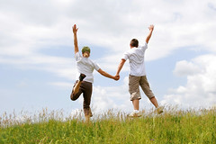 Couple jumping in the air togethe over a grassy field - shutterstock_13359127
