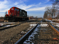 Resting in the Switch Yard (DenisGiles) Tags: railroad blue winter red sky snow ontario canada cn train canon rocks perspective engine rail chatham distance 7071 canadiannationalrailroad powershots3 denisgiles