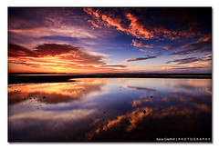 Fiery Inspiration. ([ Kane ]) Tags: sunset sky sun beach water clouds reflections photography sand rocks australia brisbane explore qld queensland kane frontpage wellingtonpoint gledhill sigma1020 50d kanegledhill wwwhumanhabitscomau kanegledhillphotography