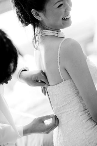 Groom adjusting bride's gown
