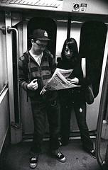 couple with free paper (teh hack) Tags: street people bw white black film subway person photography photo nikon edmonton candid nb iso transit be hp5 asa 3200 lrt ei fe2 ddx