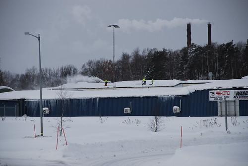 Män skottar snö på ett tak med snöslunga