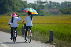 Off to School (Alex Stoen) Tags: school girls 2 two sun colors composition canon geotagged countryside education colorful flickr couleurs happiness sunny colores vietnam bicycles shade transportation uniforms ricepaddies schoolgirls ricefields indochine cycles umbrela indochina haiphong schooluniforms offtoschool fav10 goingtoschool ef70200f28lisusm 5dmk2 canon5dmarkii alexstoen alexstoenphotography hanoitohalong