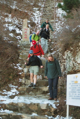 Trekkers descending icy steps at Huangya