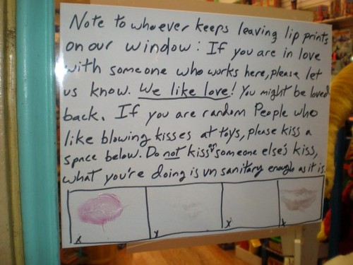 Note to whoever keeps leaving lip prints on our window: If you are in love with someone who works here, please let us know. We like love! You might be loved back. If you are random People who like blowing kisses at toys, please kiss a space below. Do not kiss on someone else's kiss, what you're doing is unsanitary enough as it is.