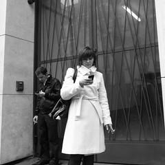 Mobile Battle (anw.fr) Tags: city blackandwhite bw woman paris mobile portable haussmann phone cigarette femme streetphotography nb smoking fumeur rue ricoh ville parisian cigaret parisienne téléphone grd