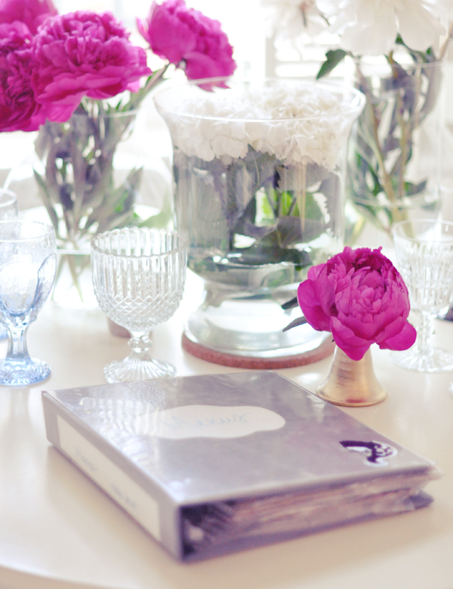 take  out menus  in a binder + pink peonies and crystal on kitchen table