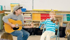 Musician Kelly Thibodeaux plays a duet with Slater Elementary School student Parker Landon, who is learning to play the fiddle. Thibodeaux has been working with the students as part of a two-week artist-in-residence program. (Photo by RANDY PARKS)