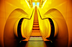 Amber Escalation (Surrealize) Tags: seattle light orange motion black reflection public glass lines yellow electric architecture bronze grate gold amber washington nikon colorful stair glow angle vibrant steel interior library escalator wide perspective illumination rail symmetry ceiling staircase railing curve elevation hdr remkoolhass d700 surrealize