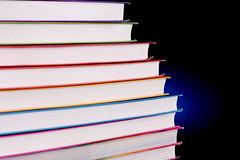 Stack of colorful books with blue light behind them