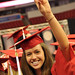 Graduate poses for a photo taken by a family member in the RBC Center seats.