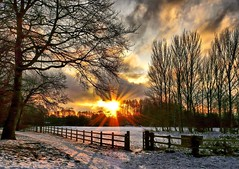 Sunrise over a snowy field (John the Neath) Tags: morning trees winter sun snow cold clouds sunrise fence bravo gate shadows panasonic tap beams countrypark monmouthshire caldicot z18 minus6