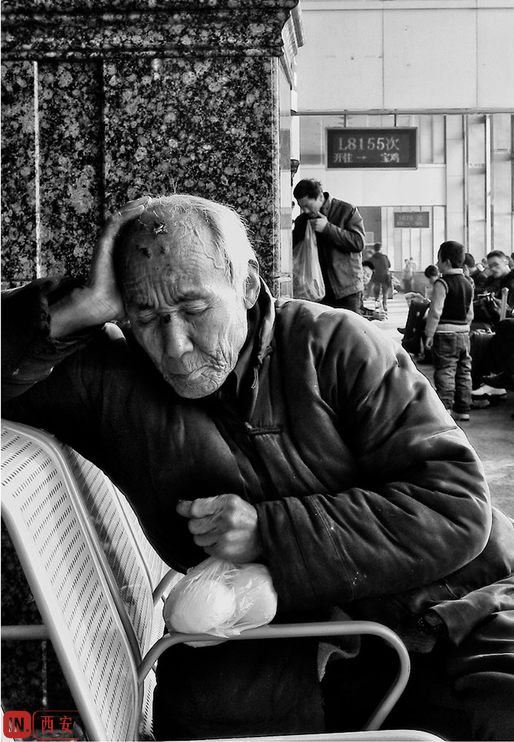 在西安火车站里疲惫打盹的老人