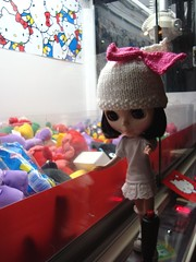Blythe playing the Hello Kitty claw game