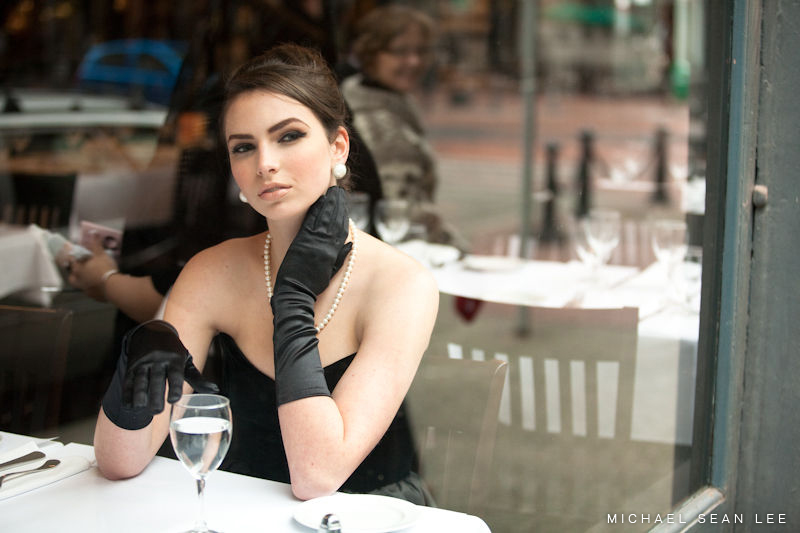 Model sitting by cafe window.