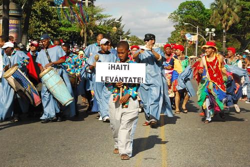 Carnaval en Haití. 2010. Un niño lleva una pancarta que dice: !Haiti levántate!