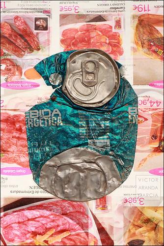 Lata aplastada sobre catálogo de Carrefour retroiluminado