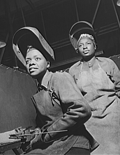 Two African-American women working in a factory during WWII.