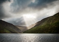 Glendalough (solecism) Tags: ireland lake mountains forest cloudy spotlight glendalough wicklow sunbeams upperlake darkandstormy boniverholocene