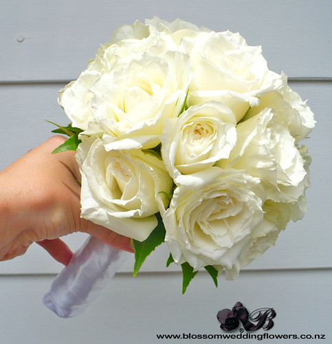 Bridesmaid bouquet with white roses cuffed with camellia leaf,