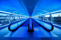 The Blue Walkway (Esther Seijmonsbergen) Tags: uk blue england manchester vanishingpoint airport cool symmetry walkway elevators connection skyway terminal2 converginglines estherseijmonsbergen walkingbelt wwwdigitalexposurephotographynl fotograafrotterdam