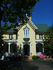 the front of the main house with green trees and pink azaleas and