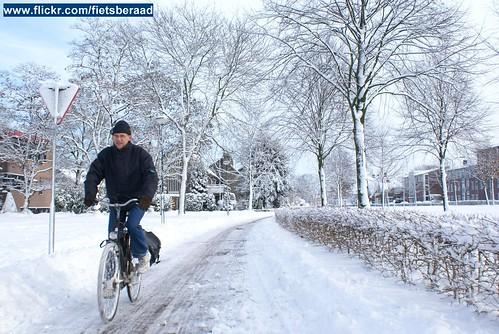 Fietser op fietspad met sneeuw